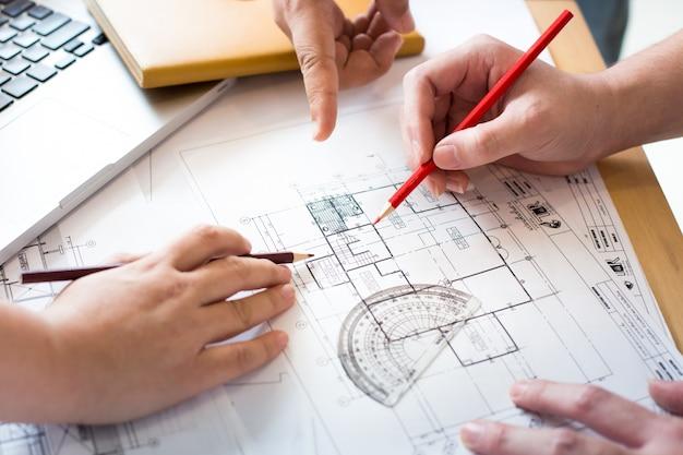 les architectes discutent la table avec un plan gros plan sur les mains et projet d. Black Bedroom Furniture Sets. Home Design Ideas