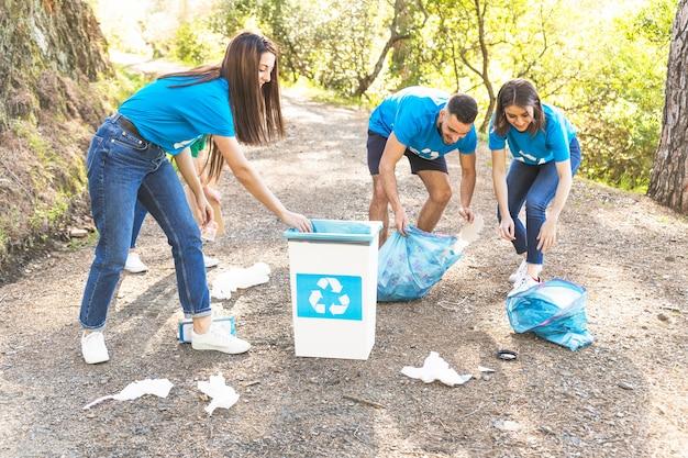 Les gens collectent des déchets dans les bois Photo gratuit
