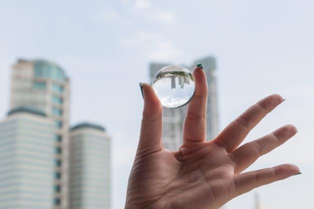 Main de femme tenant une boule de cristal avec immeuble de bureaux