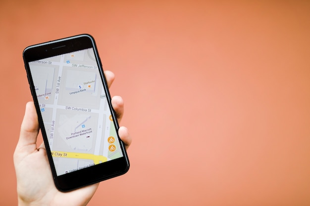 Main de l'homme tenant le téléphone mobile avec navigation GPS carte sur fond orange Photo gratuit