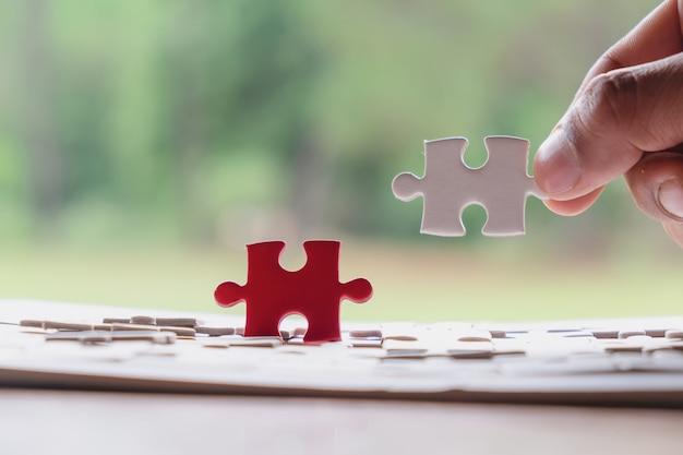 Main de mâle mettant puzzle sur le bureau en bois et fond de nature