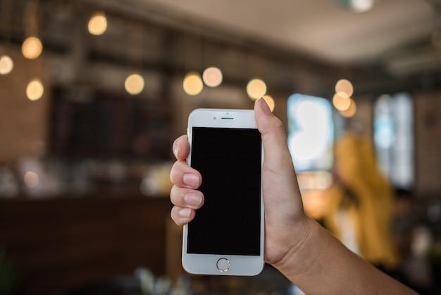 Main tenant un téléphone mobile blanc avec un écran noir blanc Photo gratuit
