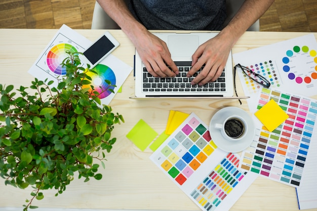 Mains d'hommes designer graphique utilisant un ordinateur portable Photo gratuit