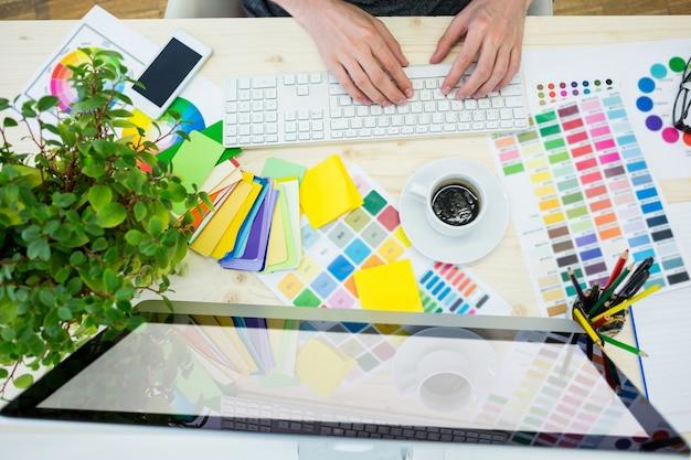 Mains de designer graphique mâle en utilisant l'ordinateur Photo gratuit