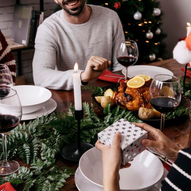 Mains tenant la boîte-cadeau au dîner de Noël Photo gratuit