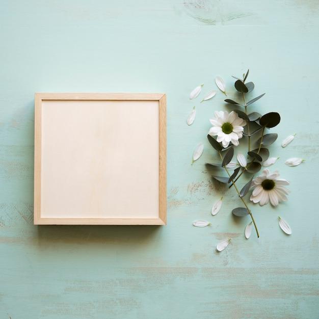 Maquette de cadre carré à côté de fleur Photo gratuit