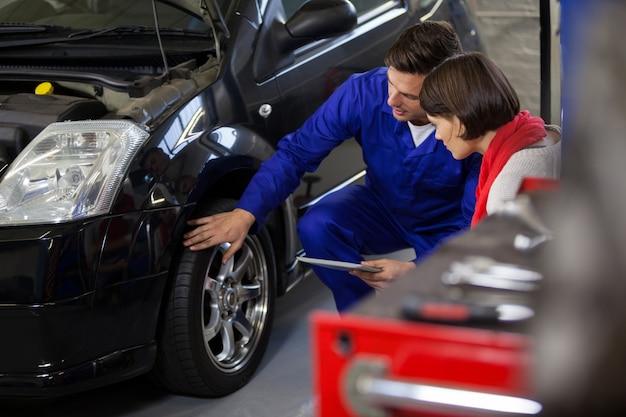 Mechanic montrant client le problème avec la voiture Photo gratuit