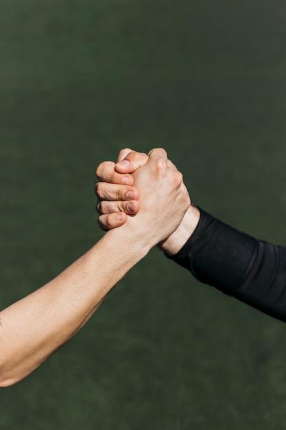 Poignée de main sur le terrain de football Photo gratuit