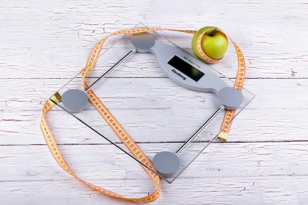 Pomme vert, ruban adhésif orange sur des balances en verre Photo gratuit