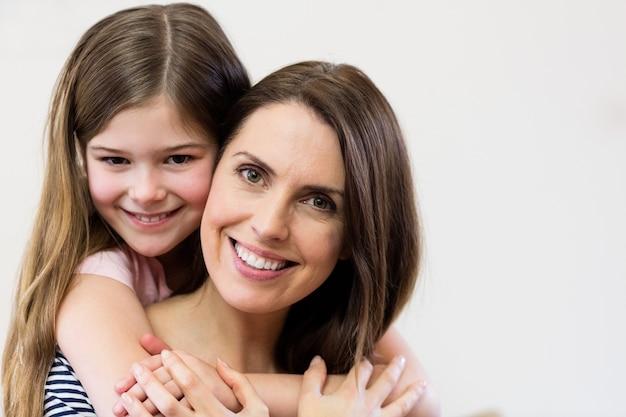 Portrait de la mère et la fille embrassant Photo gratuit