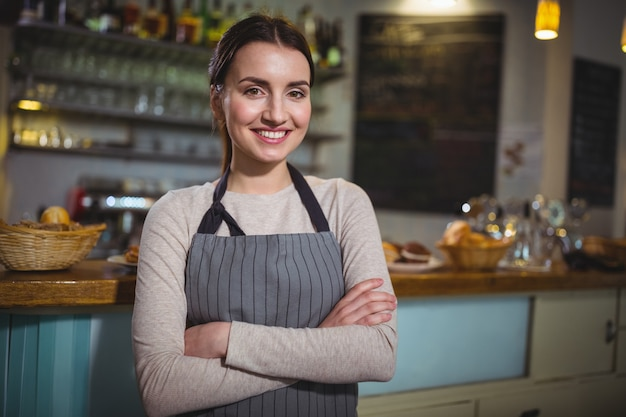 Portrait de sourire serveuse debout au comptoir Photo gratuit