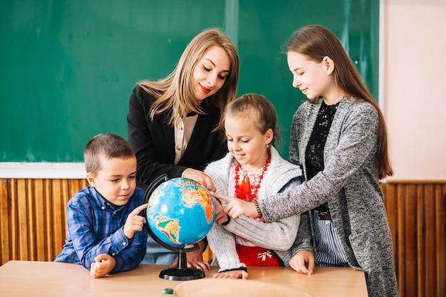 Professeur d'école et étudiants travaillant avec globe Photo gratuit