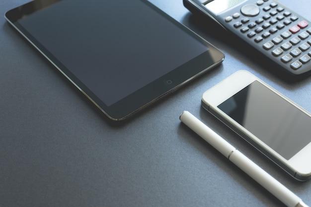 Quelques appareils électroniques affichés sur fond gris. Smart phone, pad and calculator, tous numériques sauf un stylo. Scène de travail. Photo gratuit