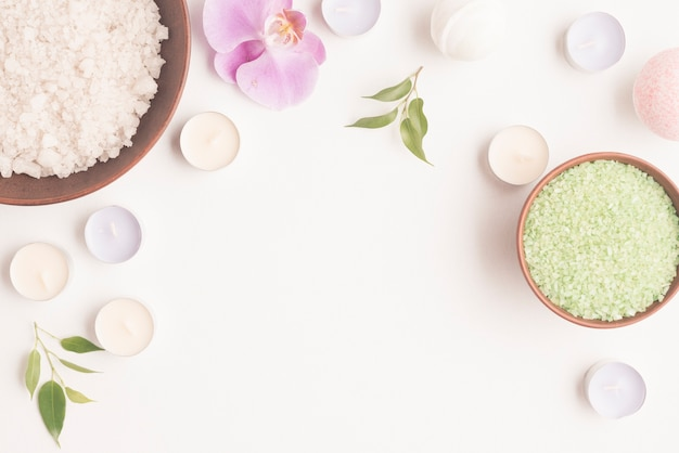 Sel pour bain aromatique dans un plat en argile orné de bougies et fleur d'orchidée sur fond blanc Photo gratuit