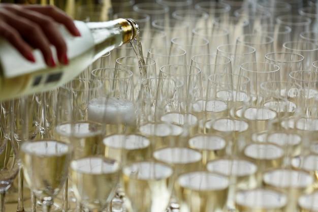Serveur verse du champagne dans les verres Photo gratuit