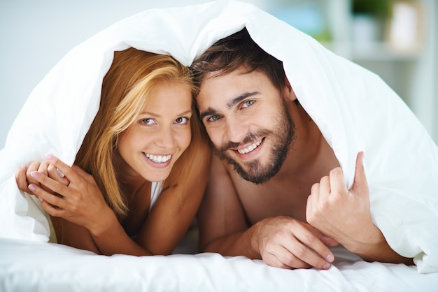 sourire couple sous la couverture dans le lit t l charger des photos gratuitement. Black Bedroom Furniture Sets. Home Design Ideas
