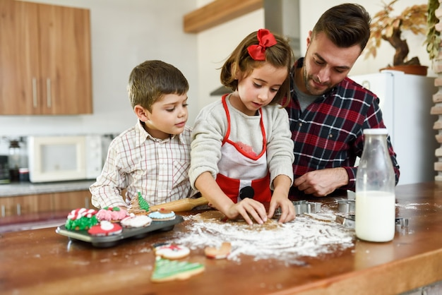 Sourire famille décorer, noël, biscuits dans la cuisine Photo gratuit