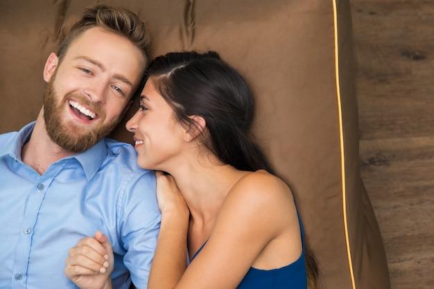 Sourire jeune couple appréciant couché sur le canapé Photo gratuit