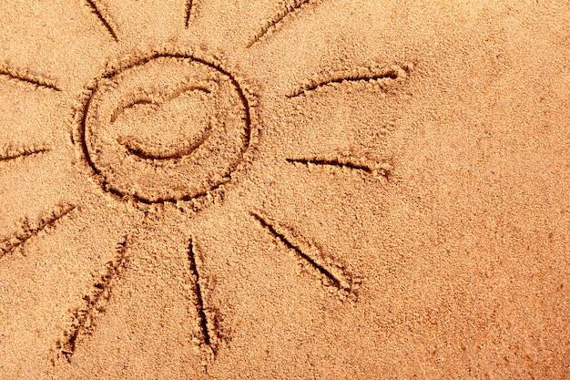 Sourire soleil dessiné sur une plage de sable Photo gratuit