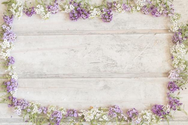 surface en bois avec cadre en fleurs violettes et blanches Photo gratuit