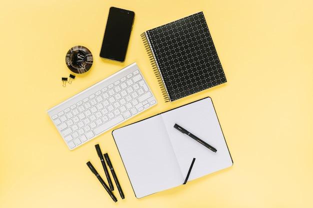 Téléphone portable et clavier blanc avec papier à lettres de bureau