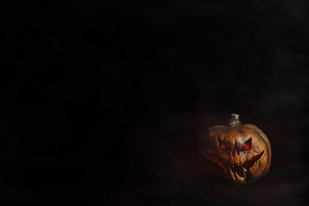 T te de citrouille d 39 halloween aux yeux rouges fond noir t l charger des photos gratuitement - Tete de citrouille ...
