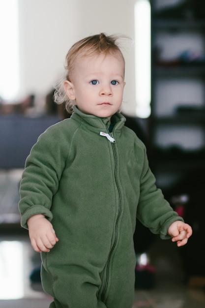 Un joli petit garçon aux sauteurs verts se tient devant le miroir Photo gratuit