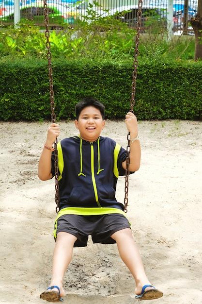 Sport Asiatique un joyeux garçon de sport asiatique joue sur une aire de jeux swing