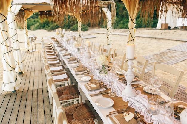 une table manger longue et blanche avec des verres tincelants et des bougeoirs se trouve sur. Black Bedroom Furniture Sets. Home Design Ideas
