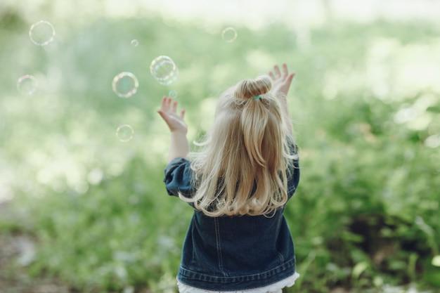 Vue arrière de la petite fille jouant avec des bulles de savon Photo gratuit