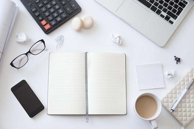Vue de dessus dun bureau de travail avec un cahier blanc ouvert