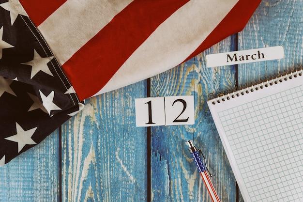 12 marzo giorno del calendario bandiera degli stati uniti d'america simbolo di libertà e democrazia con blocco note vuoto e penna sul tavolo di legno dell'ufficio Foto Premium