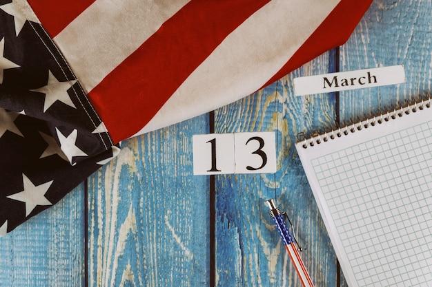 13 marzo giorno del calendario bandiera degli stati uniti d'america simbolo di libertà e democrazia con blocco note vuoto e penna sul tavolo di legno dell'ufficio Foto Premium