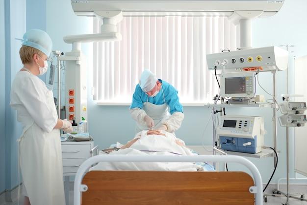 19.7.17, bielorussia, cardiocentro di grodno. anestesista medico per terapia intensiva che installa pacemaker o catetere venoso centrale Foto Premium