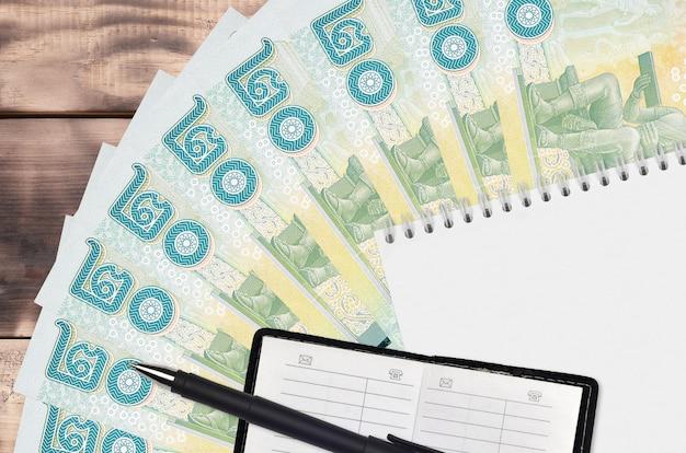Ventaglio da 20 banconote in baht thailandese e blocco note con rubrica e penna nera. Foto Premium