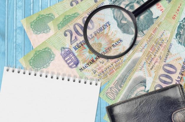 200 banconote in fiorini ungheresi e lente d'ingrandimento con borsellino nero e blocco note. Foto Premium