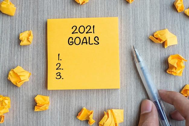 2021 parola obiettivo sulla nota gialla con imprenditore tenendo la penna e carta sbriciolata Foto Premium