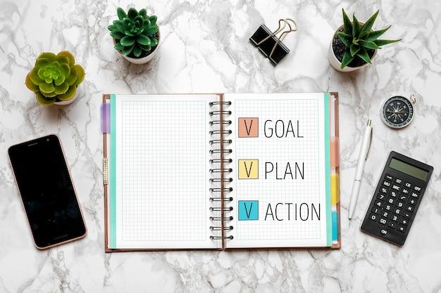 Obiettivo del nuovo anno 2021, piano, testo d'azione sul blocco note aperto, occhiali, tazza di caffè, penna, smartphone Foto Premium
