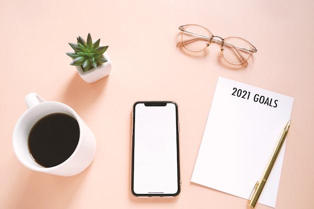 Concetto di risoluzioni del nuovo anno 2021 sulla foto piatta della scrivania dell'area di lavoro con smartphone, caffè, nota di carta con sfondo spazio copia, stile minimal Foto Premium