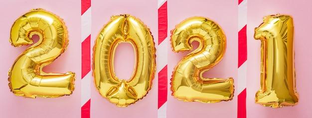 Palloncini d'oro anno 2021 con nastro adesivo di avvertenza sul rosa. mantenere il concetto di distanza sociale covid 19. Foto Premium