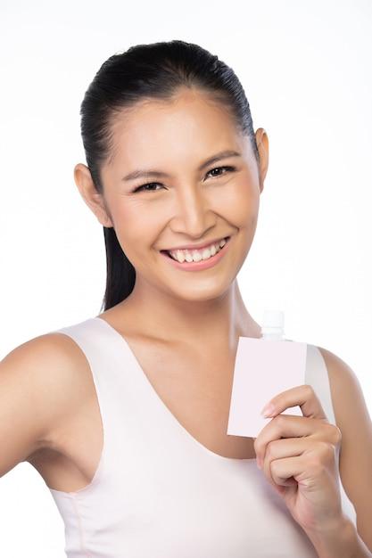 La giovane donna asiatica degli anni '20 ha una bella pelle liscia e uno sbiancamento pulito. la ragazza si sveglia al mattino e sente un sorriso fresco ridere come usando la lozione per il trattamento. Foto Premium