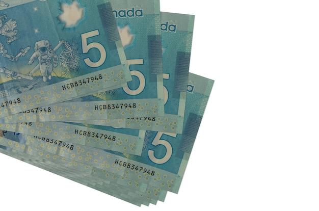 5 banconote in dollari canadesi si trovano in un piccolo mazzo o pacchetto isolato su bianco Foto Premium