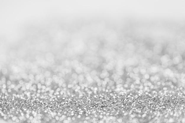 Astratto sfocato scintillante sfondo bokeh d'argento. concetto di design di decorazioni festive Foto Premium