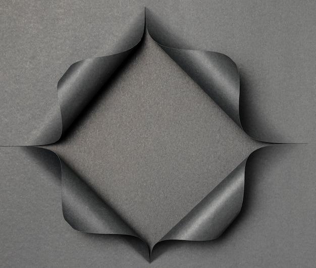 Forma grigia astratta su carta nera strappata Foto Premium