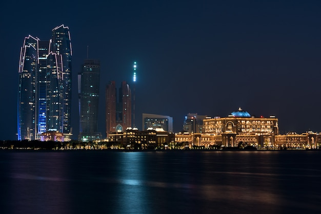 Skyline di edifici di abu dhabi dal mare di notte Foto Premium