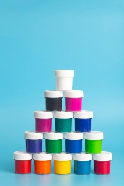 Vernice acrilica di diversi colori su sfondo blu. vernice per dipingere. Foto Premium
