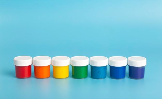 Vernice acrilica nei colori dell'arcobaleno su sfondo azzurro. vernice per la pittura, concetto di colori dell'arcobaleno. Foto Premium