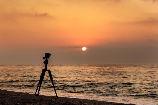 Azione fotocamera su un treppiede su una spiaggia sabbiosa che riprende un video del tramonto sul mare. Foto Premium