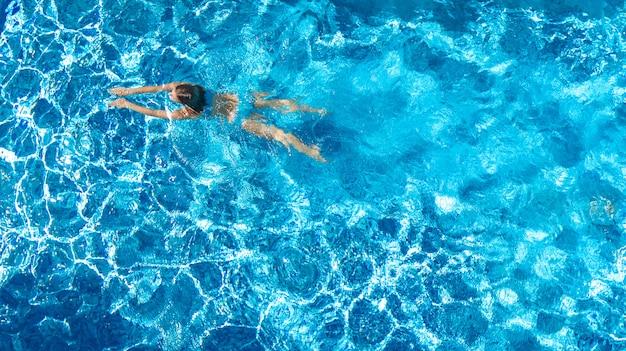 La ragazza attiva nella vista aerea del fuco della piscina da sopra, la giovane donna nuota in acqua blu, la vacanza tropicale, festa sul concetto della località di soggiorno Foto Premium