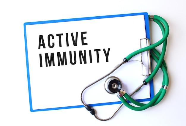 Testo di immunità attiva sulla cartella medica con documenti e stetoscopio su sfondo bianco. concetto medico. Foto Premium